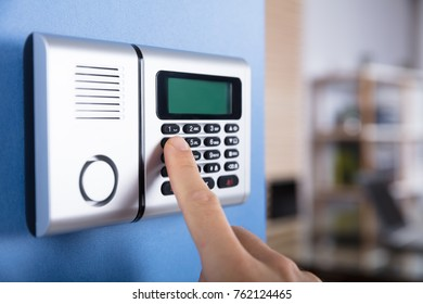 Close-up Of Person's Finger Entering Code In Security System On Blue Wall
