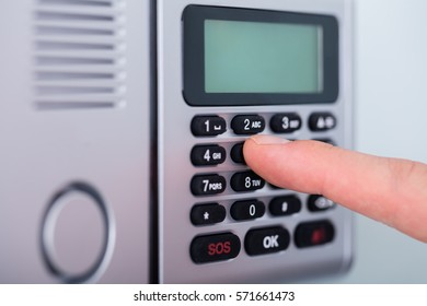 Close-up Person's Finger Setting Security Alarm System