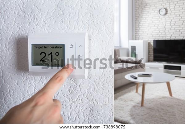 Gros plan Sur La Main D'Une Personne Réglant Le Thermostat Numérique À La Maison