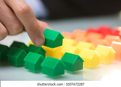 Close-up Of A Person's Hand Arranging Green House Model In A Row