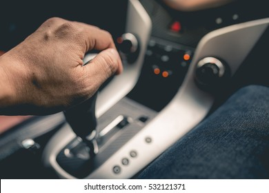 Close-up Of Person's Hand Changing Gear While Driving Car