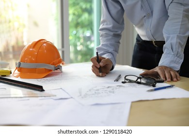 Close-up Of Person's Hand Drawing Plan construction On Blue Print with architect equipment - Image