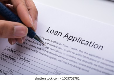Close-up Of A Person's Hand Filling Loan Application Form