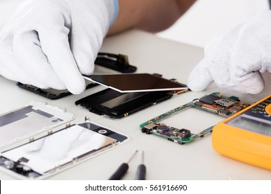 Close-up Of Person's Hand Fixing Damaged Screen On Mobile Phone
