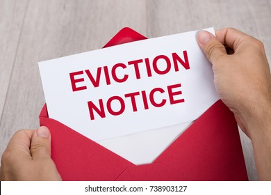 Close-up Of A Person's Hand Holding Eviction Notice In Red Envelope