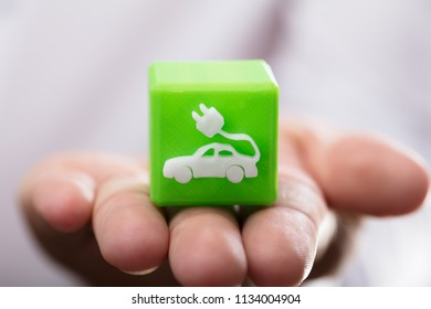Close-up of a person's hand holding green cubic block with eco car icon