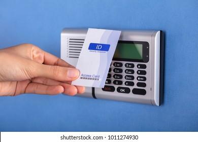 Close-up Of A Person's Hand Holding Key Card Near Security System