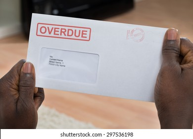 Close-up Of Person's Hand Holding Overdue Notice