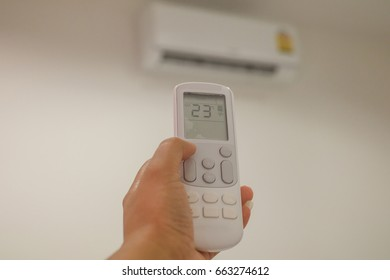 Close-up Of Person's Hand Holding Remote In Air Conditioner
