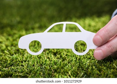 Close-up Of A Person's Hand Holding White Paper Car On Green Grass