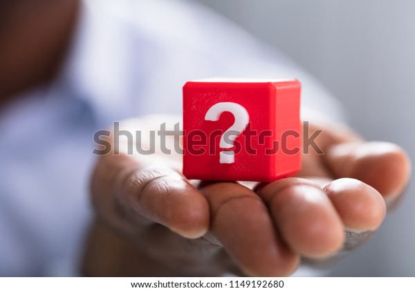 Nahaufnahme von Hand, die ein weißes Fragezeichen auf rotem Block hält