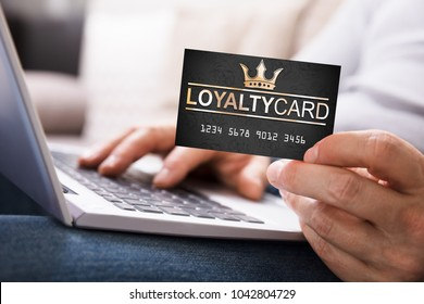 Close-up Of A Person's Hand With Loyalty Card Using Laptop