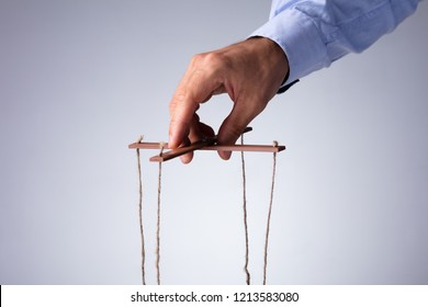 Close-up Of A Person's Hand Manipulating Marionette With String On Gray Background