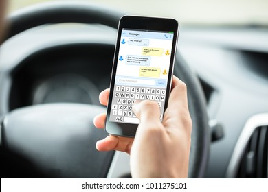 Close-up Of Person's Hand With Mobilephone Text Messaging Inside Car