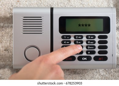 Close-up Of A Person's Hand On Security Alarm Keypad Entering The Security Code