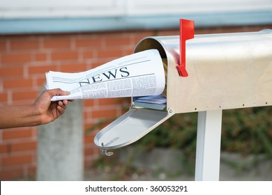 Close-up Of Person's Hand Opening Mailbox To Remove Newspaper