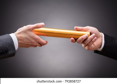 Close-up Of A Person's Hand Passing Baton To Businessperson On Grey Background