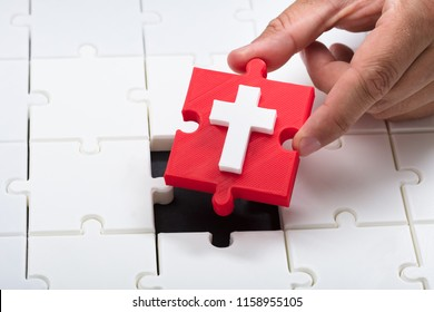Close-up of a person's hand placing red holy cross symbol piece into jigsaw puzzle