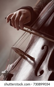 Close-up of a person's hand playing classical music on a violoncello. Musical concept
