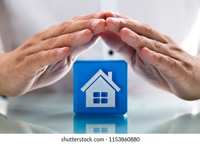 Close-up of a person's hand protecting blue cubic block with house icon