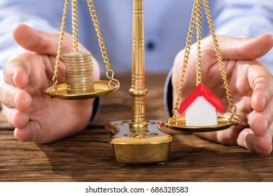 Close-up Of A Person's Hand Protecting Justice Scale With Stacked Coins And House Model