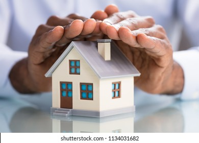 Close-up Of A Person's Hand Protecting Miniature House On The Desk