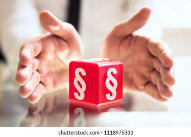 Close-up Of A Person's Hand Protecting Red Cubic Block With Paragraph Symbol