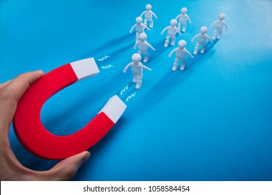 Close-up Of A Person's Hand Pulling Human Figures With Horseshoe Magnet On Blue Background