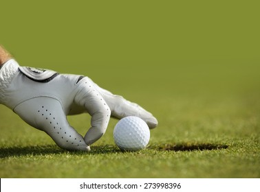 Close-up of a person's hand putting a golf ball near a hole