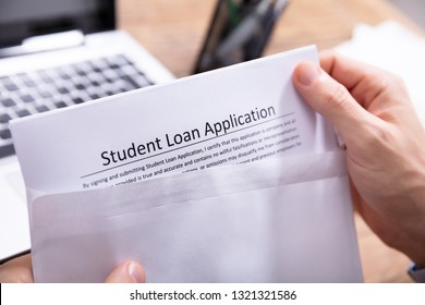Close-up Of A Person's Hand Removing Student Loan Application Form From White Envelope