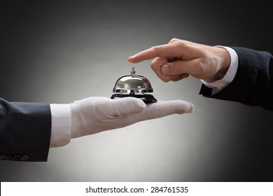 Close-up Of A Person's Hand Ringing Service Bell Hold By Waiter