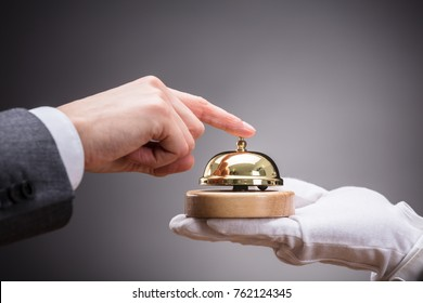 Close-up Of Person's Hand Ringing Service Bell Held By Waiter On Grey Background