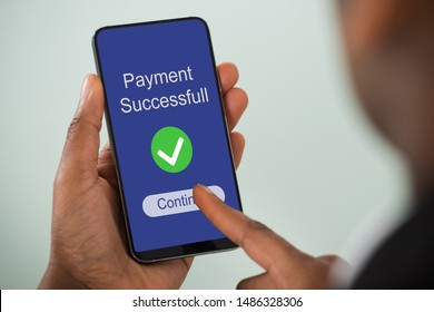 Close-up Of Person's Hand Showing Payment Successful Message On Mobilephone Screen