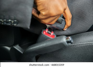 Close-up Of Person's Hand Sitting In Car Fastening Seat Belt
