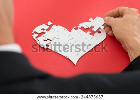 Close-up Of A Person's Hand Solving Heartshape Jigsaw Puzzle