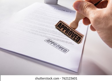 Close-up Of Person's Hand Stamping Approved On Contract Paper