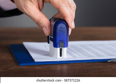 Close-up Of A Person's Hand Stamping Document On Wooden Desk