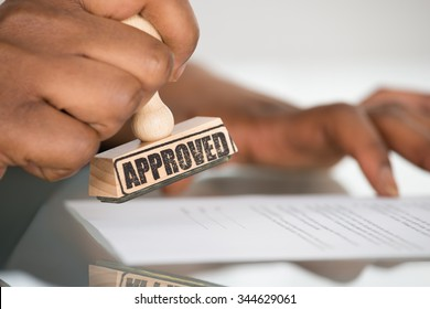Close-up Of A Person's Hand Stamping On Approved Contract Form