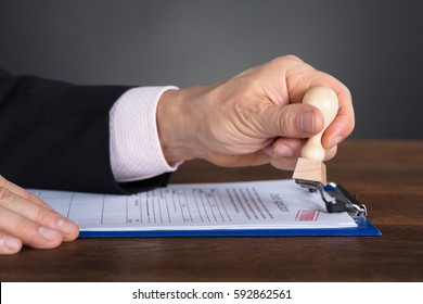 Close-up Of A Person's Hand Stamping On Approved Application Form