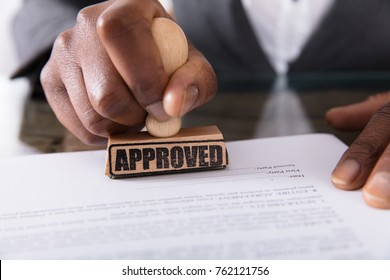 Close-up Of A Person's Hand Stamping On Approved Contract Form On Desk