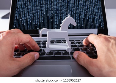 Close-up Of A Person's Hand With Trojan Horse Icon On Laptop Affected By Virus