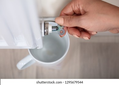 Close-up Of A Person's Hand Turning Radiator Bleed Valve To Release Air With Cup