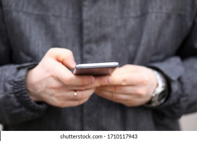Close-up of persons hand using device for communication. Mobile phone for fun and entertainment. Man using modern gadget. Technology and addiction concept