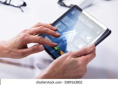 Close-up Of A Person's Hand Using Home Control System On Digital Tablet