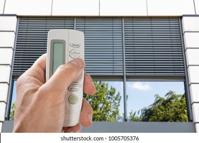 Close-up Of A Person's Hand Using Remote To Open Window Shutter