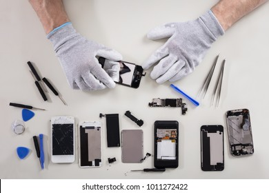 Close-up Of A Person's Hand Wearing Gloves Repairing Mobile Phone