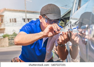 Close-up Of Person's Young Man Locksmith Hand Opening Bronze Car Door With Lock picker. Locksmith door opening device