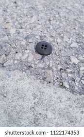 Closeup perspective of a lost worn black clothing button found laying on a weathered concrete parking area. Part of a white paint strip in the foreground.