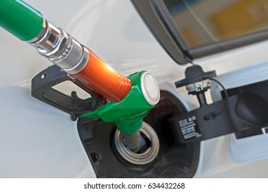 closeup petrol nozzle pumping unleaded gasoline to fuel tank of car. Car at the fuel station.