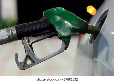A close-up of a petrol pump while get petrol in a car
